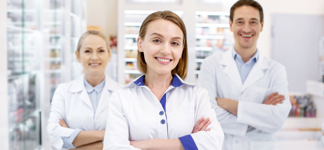 Jolly three pharmacists crossing arms while staying in drugstore.