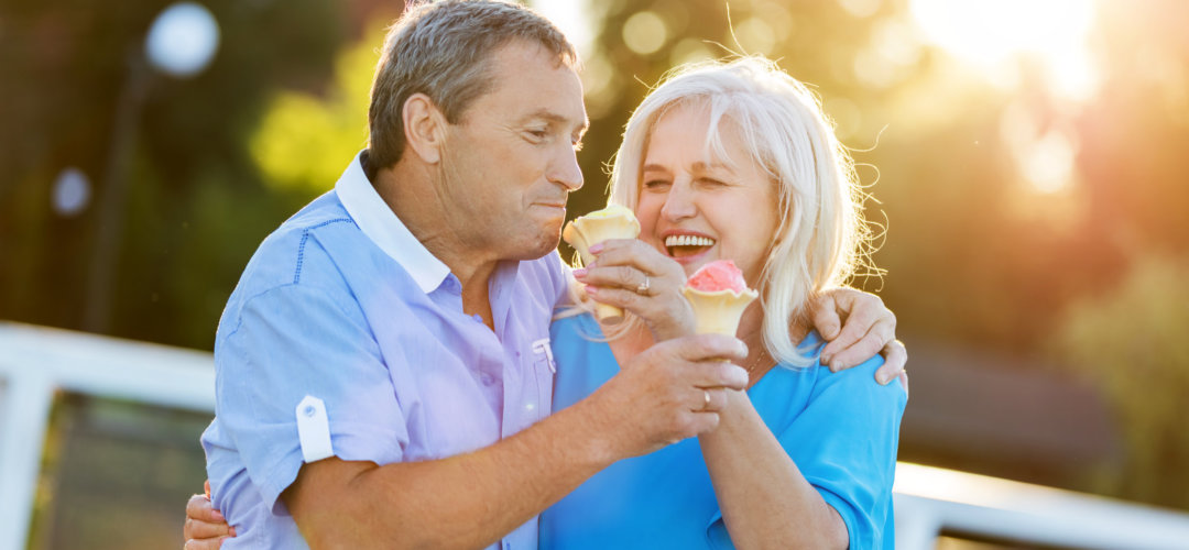 Senior couple hugging and laughing together, eating ice cream.